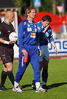 Trener Ivar Morten Normark, Aalesund, følger en skadet Erlend Holm, Aalesund, av banen. <br /> <br /> Fotball: Kongsvinger - Aalesund 2-2 (5-2 e. straffer). NM 2004 herrer, 3. runde. 8. juni 2004. (Foto: Peter Tubaas/Digitalsport.
