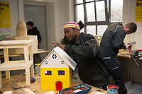 DEU, Deutschland, Germany, Berlin, 17.12.2015: Flüchtlinge arbeiten in einer Werkstatt der Flüchtlings-Initiative der Handwerkskammer, arrivo Berlin, in der Innung für Metall- und Kunststofftechnik. Hessan Adam aus Ghana beim Streichen eines Holzhauses.