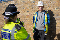 © Licensed to London News Pictures. 04/10/2021. London, UK. An arrested activist from Insulate Britain at the entrance to the Blackwall tunnel after the group blocked the tunnel earlier this morning. Insulate Britain have successfully blocked various roads around the capital over a number of weeks, resulting in a court injunction banning them from going near the M25 motorway.  Photo credit: George Cracknell Wright/LNP