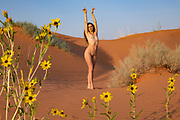 Nude woman posing in sand dunes in Moab, Utah with wildflowers in the foreground