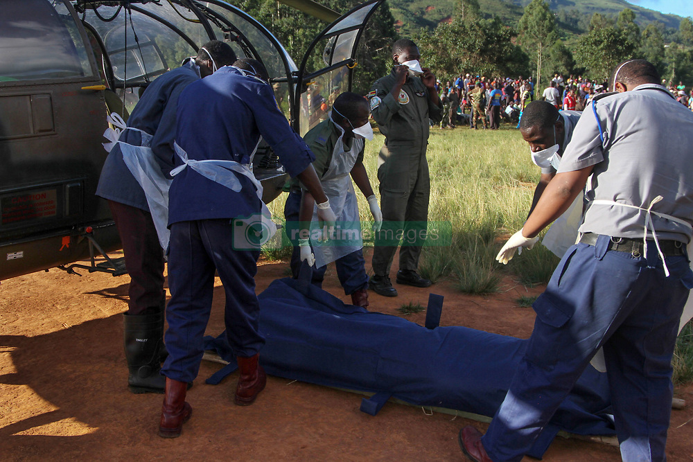 March 22, 2019 - Chimanimani, Zimbabwe - Zimbabwean police wearing dust masks carry a dead body recovered from a nearby river to a helicopter after cyclone Idai struck the area. Five days after tropical cyclone Idai cut a swathe through Mozambique, Zimbabwe and Malawi, the confirmed death toll stood at more than 300 and hundreds of thousands of lives were at risk, officials said. (Credit Image: © Tafadzwa Ufumeli/ZUMA Wire)