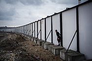 A migrant from Afghanista is seen crossing a construction yard fence in Belgrade makeshift camp. Belgrade, Serbia. March 19th, 2017. Federico Scoppa