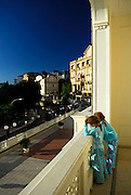 Two children (9 years old, 5 years old) dressed in pyjamas, leaning on hotel balcony in early morning sunlight, overlooking street in Opatija, Croatia