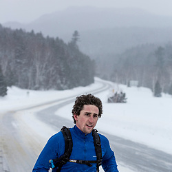 A man running on NH 16 in New Hampshire's White Mountains on a snowy winter day.