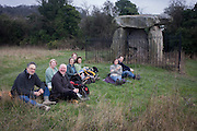 A group of ramblers rest for lunch at the ancient stones of Kit's Coty, Kent, England. Kitts Coty is the name of the remains of a Neolithic chambered long barrow on Blue Bell Hill near Aylesford in the English county of Kent.