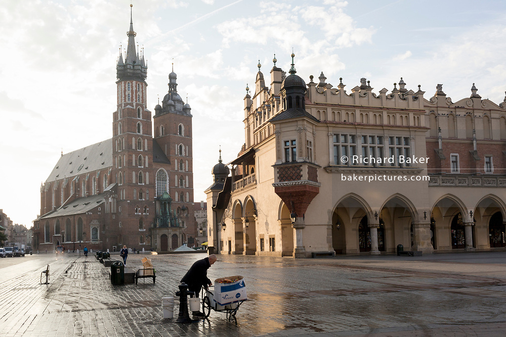 A flower seller fills buckets with fresh water beneath the towers of the Church of St Mary (left) and the Cloth Hall on Rynek Glowny market square, on 23rd September 2019, in Krakow, Malopolska, Poland.