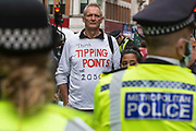 An environmental activist from Extinction Rebellion wears a t-shirt referring to climate tipping points during the first day of Impossible Rebellion protests on 23rd August 2021 in London, United Kingdom. Extinction Rebellion are calling on the UK government to cease all new fossil fuel investment with immediate effect.