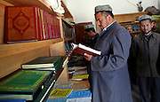 Uyghur men look at islamic texts at a bookshop in the city of Hotan in China's western Xinjiang province. Hotan was and still is a center of Islam in Xinjiang. By most accounts, China is considered a repressive and destructive influence on local culture and religion but an energetic and positive force in terms of economic development. Children in Xinjiang are not allowed to attend Islamic school until the age of 18, and they do not have leave to attend prayers on Friday due to school. This grates on locals who see Islam as the core of their culture.