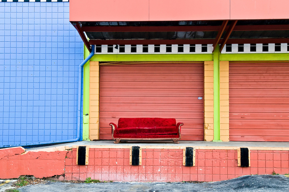 USA, Vereinigte Staaten von Amerika, Florida,Tallahassee, Rotes Sofa steht ausrangiert vor einem Künstleratelier auf dem Gelände des Rail Road Square eines ehemaligen Eisenbahngelaendes in dem nun Kuenstlerateliers untergebracht sind.2008,  www.railroadsquare.com |  USA United States of America ,Railroad Square encompasses 10 acres in downtown Tallahassee, the previous site of the historic McDonnell lumber yard, which became the Downtown Industrial Park in the 1960's under owner William J. Boynton, Jr. In the mid-1970s his daughter, Nan Boynton, re-envisioned the park as a mecca for artist's studios and galleries and began to manifest this plan, replacing industrial tenants with regional artists looking for inexpensive studio spaces, including Florida State University's studio artist program