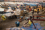 A woman seating on a matress in Mopti's harbour. At the confluence of the Niger and the Bani rivers, between Timbuktu and Ségou, Mopti is the second largest city in Mali, and the hub for commerce and tourism in this west-african landlocked country.
