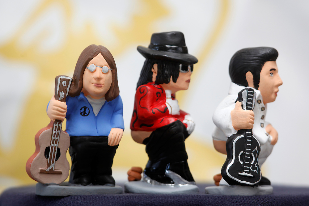 """November 10,  2010. A company in Torroella de Montgrí (Girona, Spain) called """"Caganer.com"""", which specializes in the production of """"caganers"""", unveiled today its new figurine for Christmas, Michael Jackson, Josn Lennon or prince Charles. .A """"Caganer"""" is a small figure from Catalonia, usually made of fired clay, which depicts as squatting person in the act defecating..""""Caganer"""" is Catalan for pooper. It forms part of one of the typical figures of the manger or """"Nativity"""" scene together with Mary, Joseph and the baby Jesus but hidden in a corner. It is a humorous figure, originally portraying a peasant wearing a """"barretina"""" (a red stocking hat), and seems to date from the 18th century when it was believed that the figure's deposits would fertilize the earth to bring a prosperous year. With the course of time, the original personage of this pooping figure was substituted with personalities from the political and sports worlds and other famous personalities..From left to right singers John Lennon, Michael Jackson and Elvis Presley."""