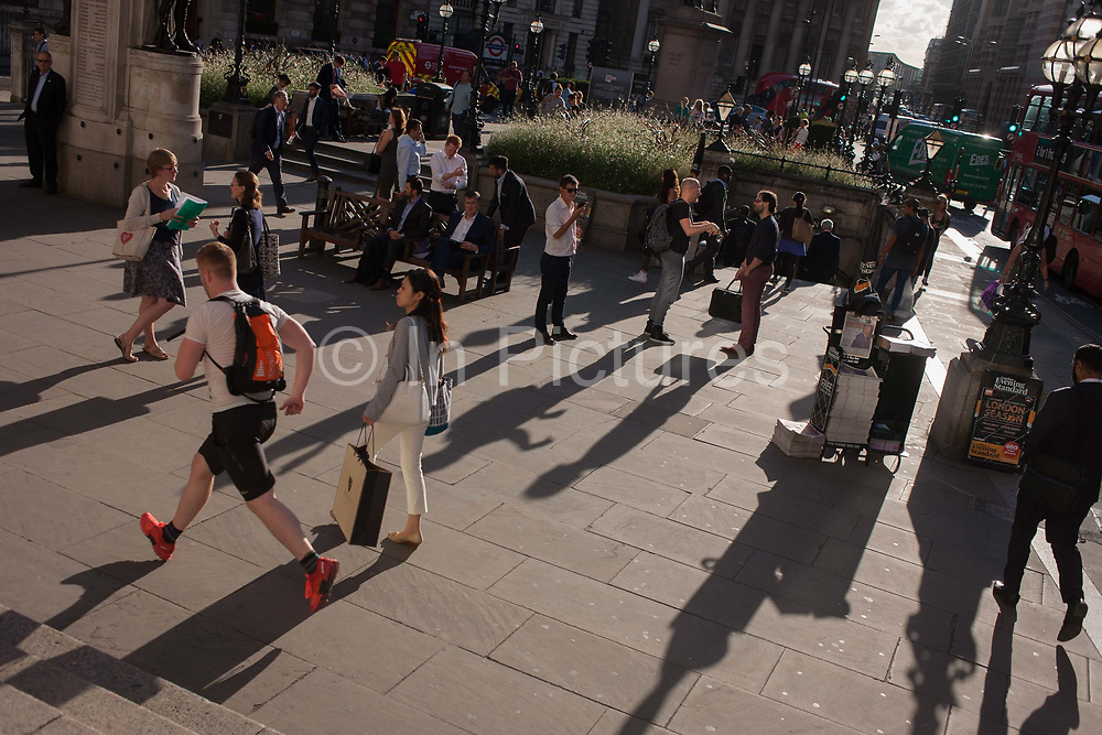 A jogger runs through Bank Triangle while a rush-hour crowd of commuters gather to meet and sit in late summer sunshine, on 8th September 2016, in the City of London, England UK. It is rush hour and commuters are beginning their journeys home from the heart of the capitals financial district, founded by the Romans in the first century.