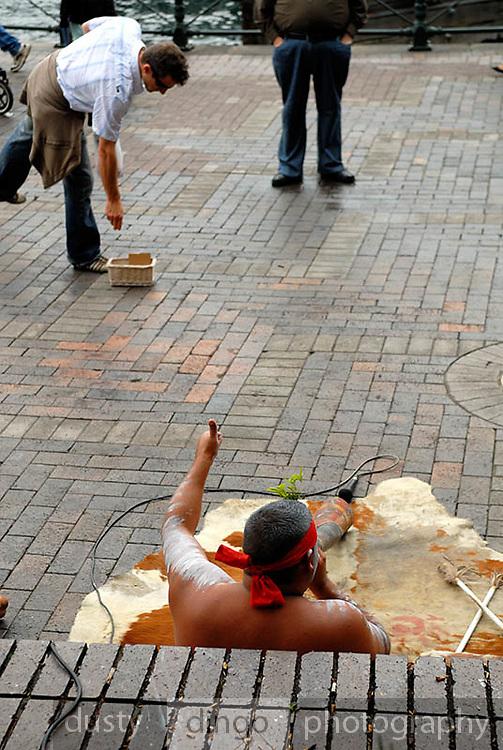 Man dropping money into hat of aboriginal busker playing didjeridoo. Circular Quay, Sydney, Australia