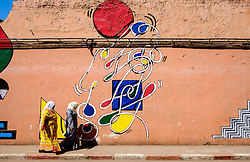 Two women in traditional dress walk past a painted wall in the Mellah district of Marrakech, Morocco, North Africa<br /> <br /> (c) Andrew Wilson | Edinburgh Elite media