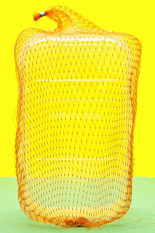 empty fruit basket with orange net object on yellow green background
