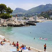 People bathing in Cote de Azur public beach. Riviera seashore in Nice, France.