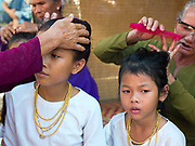 In Van Lam village, Ninh Thuan province, Central Vietnam, Cham girls usually in groups of around 5, undergo a Karoh (maturity) ceremony, one of the most important ritual events of their lives and if it has not taken place, the girl cannot marry. After a purification ritual, the girls prepare for the main ceremony by dressing in a white dress and then putting on bronze, copper and sometimes gold jewellery. The girl's hair is brushed and put up into a bun. Afterwards each girl is given a traditional yellow robe and her head is covered with a red woven cloth and then the head priest places his hand on the girls head, recites a prayer and cuts a small lock of her hair. The Cham, a Muslim community of around 39,000 people living along the coast of Central Vietnam are one of the 54 ethnic groups recognised by the Vietnamese government.