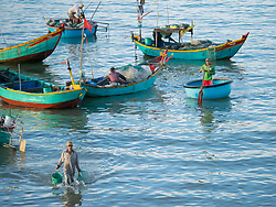 Asia, Vietnam, Mui Ne. Fishermen in traditional round fishing boats called coracles.