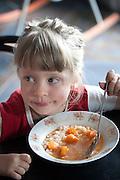 Cute young girl age 5 enjoying a traditional Polish tomato soup with carrots. Zupa pomidorowa. Zawady Central Poland