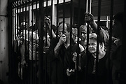 """Athens, Greece - A group of people waiting for food delivery at the gates of KYADA, Municipal Center, an organization helping the needy and homeless in Athens. Approximately 1500 meals are distributed daily. According to KYADA, this number falls far short of needs. Greek economical crisis started in 2008. The so-called Austerity measures imposed to the country by the """"Troika"""" (European Union, European Central Bank, and International Monetary Fund) to reduce its debt, were followed by a deep recession and the worsening of life conditions for millions of people. Unemployment rate grew from 8.5% in 2008 to 25% in 2012 (source: Hellenic Statistical Authority). <br /> Bruno Simões Castanheira"""