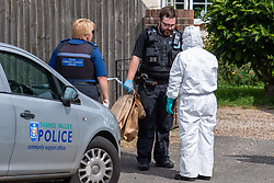 © Licensed to London News Pictures. 27/07/2021. Stoke Poges, UK. A forensic investigator and uniformed officer gather evidence at a property on Bells Hill in Stoke Poges, Buckinghamshire, following an assault on Monday 26 July at approximately 21:30BST. A man in his twenties suffered a serious leg injury following the assault which is understood to have involved a machete. Two men, aged 19 and 21, and a 20-year-old woman have been arrested on suspicion of section 18 wounding with intent. Photo credit: Peter Manning/LNP