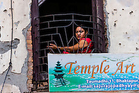 Woman looking out of a window, Bhaktapur, Kathmandu Valley, Nepal.