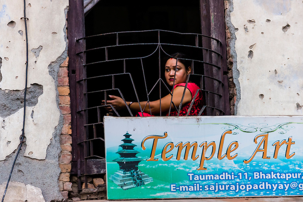 Woman looking out of a window, Bhaktapur, Kathmandu Valley, Nepal.