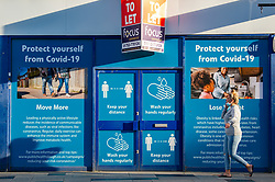 © Licensed to London News Pictures. 23/10/2020. Slough, UK. A woman talking on a mobile phone walks past an empty shop with coronavirus safety advice covering the windows. Slough will move to Local COVID Alert Level: High (Tier 2) at 00:01 BST on Saturday 24th October 2020 after an increase in people infected with the COVID-19 coronavirus. Photo credit: Peter Manning/LNP