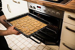 Man inserting baking tray in oven for baking cookies, Munich, Bavaria, Germany