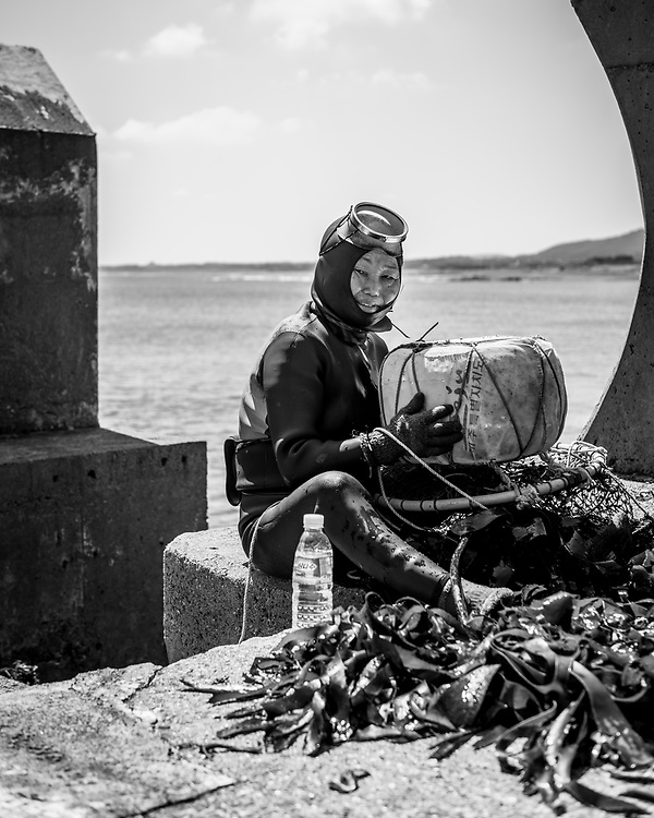 A haenyeo — that is, a traditional female diver on Jeju Island — sifts through her catch at Seongsan on Jeju Island, South Korea. The divers harvest a variety of mollusks, seaweed, and other sea life from the ocean. (September 14, 2019)