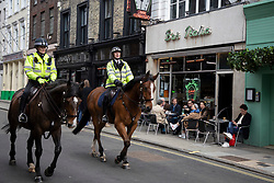 © Licensed to London News Pictures. 12/04/2021. London, UK. Mounted police patrol as members of the public eat and drink at tables outside Little Italy in Soho in central London. From today restaurants will reopen with outdoor dining following the easing of lockdown restrictions. Photo credit: George Cracknell Wright/LNP