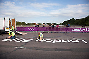 London, UK. Saturday 28th July 2012. On Putney Bridge in London, staff install a London 2012 logo onto the road prior to the Men's Team Road Race.
