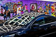 Car passing graffiti wall on construction hoarding in Great Eastern Street East London.