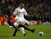 Photo: Chris Ratcliffe.<br /> Arsenal v Real Madrid. UEFA Champions League. 08/03/2006.<br /> Roberto Carlos is tackled by Emmanuel Eboue
