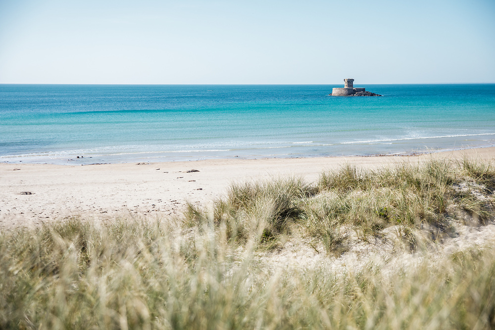 Views from the sand dunes of crystal clear,  turquoise, calm water surrounding the landmark La Rocco Tower at St ouen's Bay in Jersey, Channel Islands