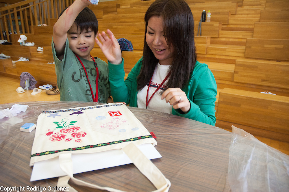 Ren (left) and his mother Yoko Kato decorate a paperbag during a summer camp for children from Fukushima, Japan..