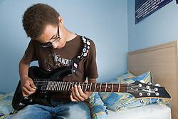 Teenage boy playing his Guitar,