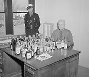 0606-M02.  Woodward, Oklahoma police department, liquor bottles on desk. Early 1950s