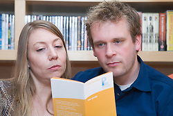 Younger couple reading pension advice leaflets so they can plan for their retirement,