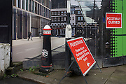 Crossrail construction hoarding of Smithfield scene placed alongside real street signs and bollard