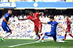Chelsea's Cesc Fabregas (right) and Liverpool's Georginio Wijnaldum (centre) battle for the ball during the Premier League match at Stamford Bridge, London.