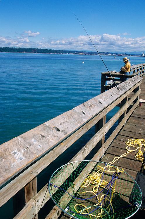 North America, USA, Washington, Tacoma. Man fishing from pier