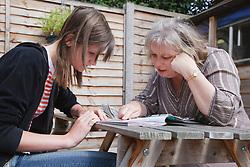 Woman and teenage girl looking at magazine.