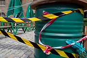 As the UK's Conornavirus pandemic lockdown continues, but with travel restrictions and social distancing rules starting to ease after three months of closures and isolation, hazard tape is still stretched across the entrance of an outdoor cafe at West India Quay in London Docklands, on 9th June 2020, in London, England.