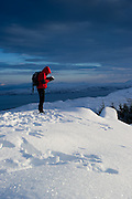 Women Looking at Snow against background of Sea and mountains. Old man of Storr, Isle of Skye, Scotland.