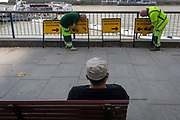 Workmen with a pedestrian diversion arrows signs overlooking the river Thames, on 1st September 2017, on the Southbank, in London, England.