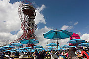 Spectators rest under branded brolleys and the artwork known as The Orbit tower in the Olympic Park during the London 2012 Olympics. Standing 115 metres high, the Orbit is the tallest art structure in Britain - offering views over the Olympic Stadium, Olympic Park and the whole of London. Located in Orbit Circus in the south of the Olympic Park, the Orbit is London's major new visitor destination by the artist Anish Kapoor. This land was transformed to become a 2.5 Sq Km sporting complex, once industrial businesses and now the venue of eight venues including the main arena, Aquatics Centre and Velodrome plus the athletes' Olympic Village. After the Olympics, the park is to be known as Queen Elizabeth Olympic Park.