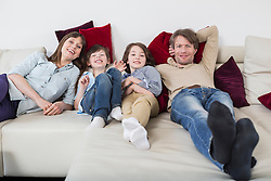 Portrait of family lying on couch, smiling