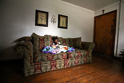 09 July 2006 - New Orleans - Louisiana. Finding Faith. Faith Figueroa. A day in the life of. Faith sits alone on the couch early in the morning.<br /> Following a ten month search for the little girl whose face appeared on the Sept 19th, 2005 cover of Newsweek magazine, Faith's mother, Miriam Figueroa has returned to town with her three children. Faith, (1 yrs), Anfernya (5yrs) and Jacquelyn (13 yrs). Credit; Charlie Varley/Sipa Press.
