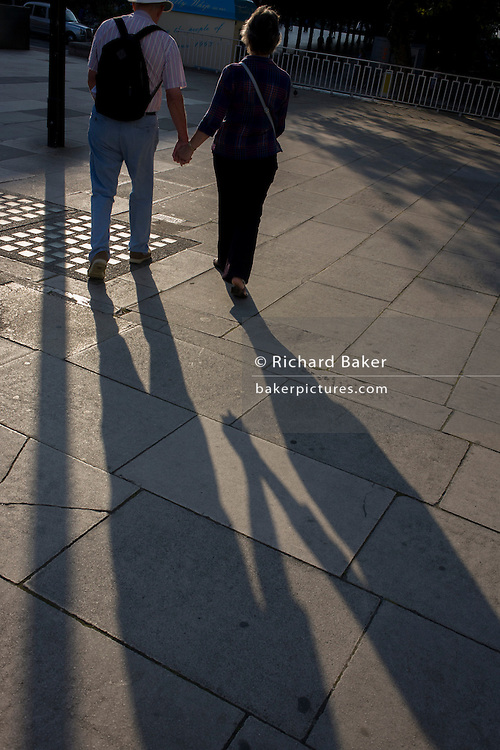 Mature couple walk on London's Southbank in late afternoon.